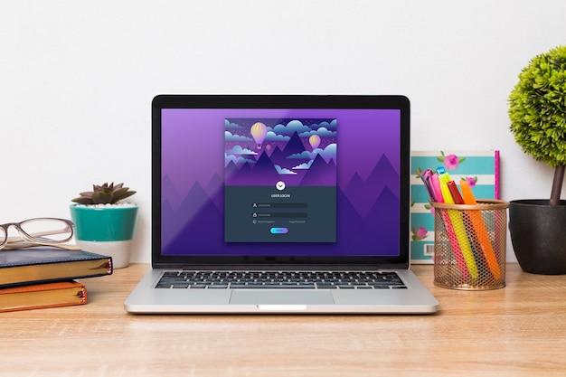 Vista frontal do laptop na mesa com canetas e agendas
