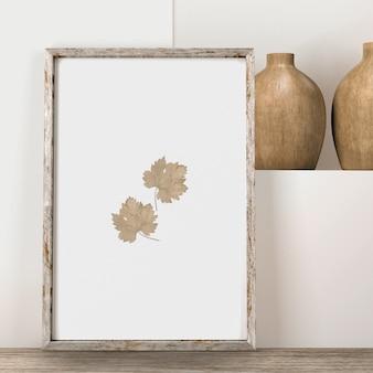 Vista frontal do quadro com folhas e vasos