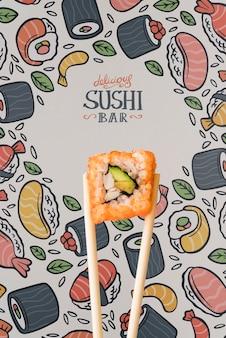 Vista frontal do sushi e pauzinho em fundo colorido
