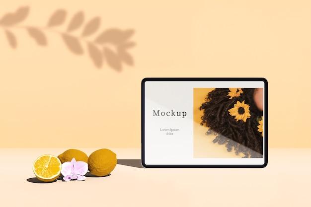 Vista frontal do tablet com frutas cítricas e sombra