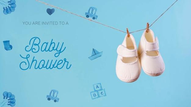 Vista frontal dos sapatos e convite para chá de bebê