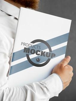 Vista frontal homem segurando um notebook mock-up