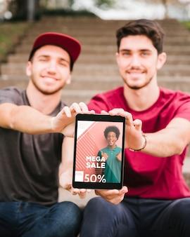 Vista frontal jovens com tablet ao ar livre