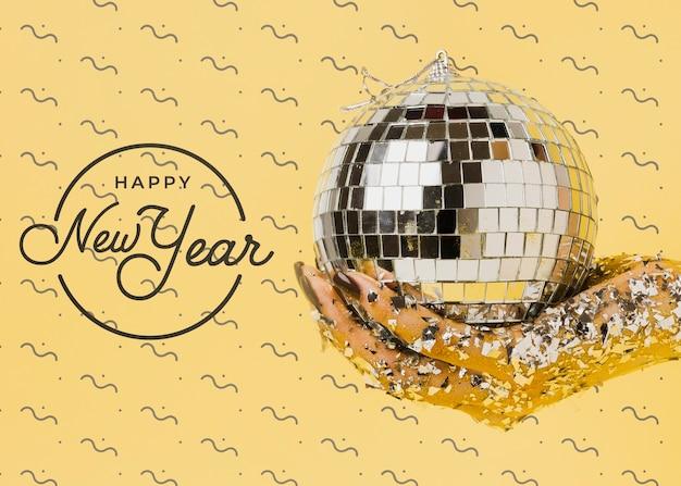 Vista frontal mulher segurando bola de discoteca com letras de ano novo