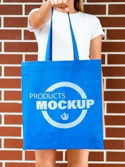 Vista frontal mulher segurando uma sacola azul lisa
