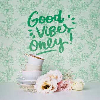 Vista frontal xícaras e flores com citação motivacional