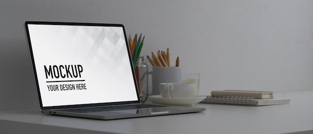 Vista lateral da área de trabalho com simulação de laptop, artigos de papelaria e suprimentos em home office conceito branco