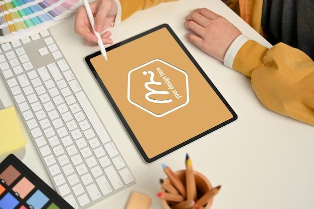 Vista lateral da mão da designer feminina trabalhando com tablet digital