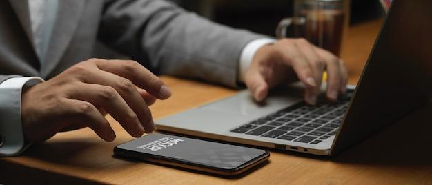 Vista lateral da mão do empresário trabalhando com maquete de smartphone