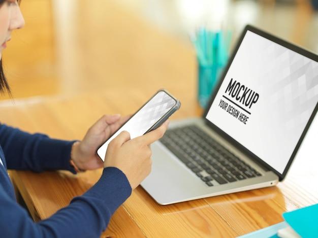 Vista lateral da mulher de negócios usando o smartphone enquanto trabalha com a maquete do laptop