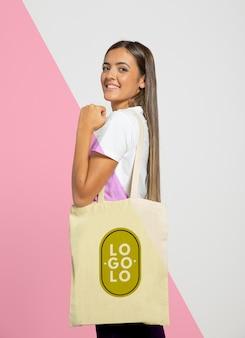 Vista lateral da mulher segurando o saco de compras