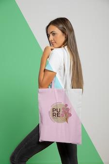Vista lateral da mulher segurando o saco