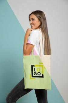 Vista lateral da mulher sorridente segurando o saco