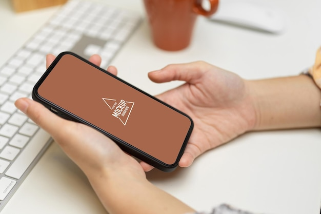 Vista lateral de mãos femininas segurando uma maquete de smartphone