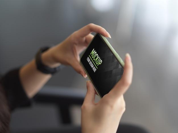 Vista lateral de mãos femininas segurando uma maquete horizontal de smartphone