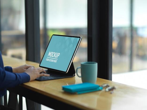 Vista lateral de mãos femininas trabalhando com maquete de tablet digital