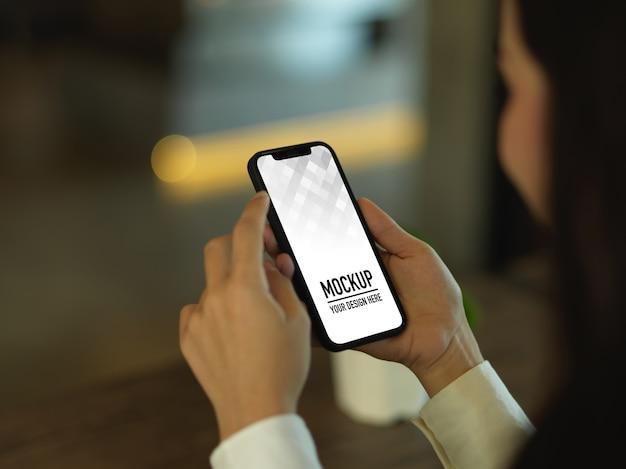 Vista lateral de mãos femininas usando maquete de smartphone