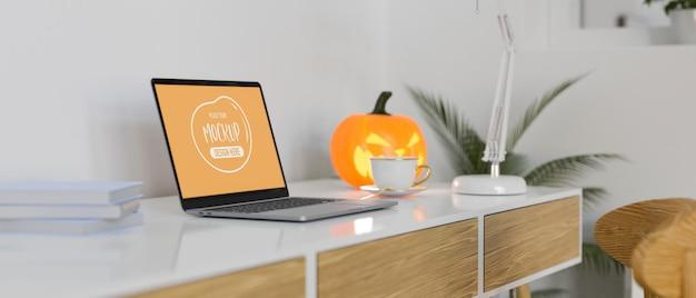 Vista lateral de um espaço de trabalho moderno com suprimentos para laptop e decorações para o dia das bruxas
