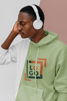 Vista lateral de um homem estiloso com capuz e fones de ouvido