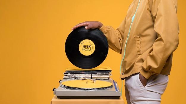 Vista lateral de um homem segurando um disco de vinil para uma maquete de loja de música