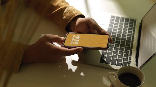 Vista lateral de uma mão masculina segurando um smartphone na área de trabalho com o laptop e a xícara de café