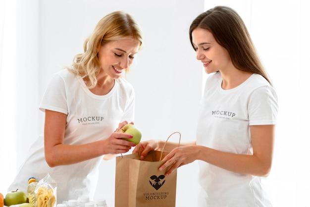 Vista lateral de voluntárias preparando sacola de doações com alimentos
