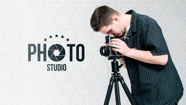 Vista lateral do fotógrafo trabalhando com câmera