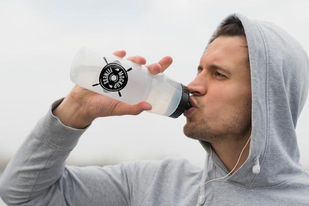 Vista lateral do homem bebendo água enquanto faz exercícios