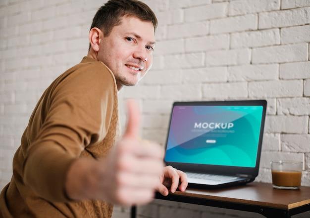 Vista lateral do homem desistindo polegares enquanto trabalha em casa
