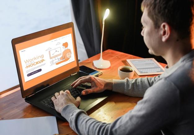 Vista lateral do homem trabalhando em casa, no laptop