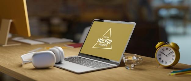 Vista lateral do laptop maquete de tela vazia e fone de ouvido despertador copo de água na mesa de madeira