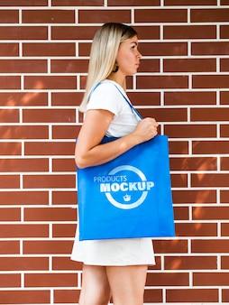 Vista lateral mulher segurando uma sacola azul simples