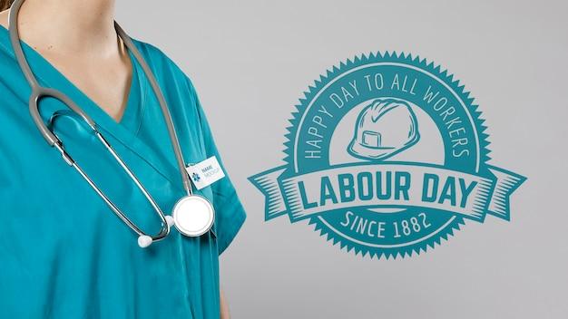Vista média da mulher com estetoscópio e crachá do dia do trabalho