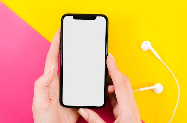 Vista superior com mãos segurando uma maquete de smartphone com fones de ouvido