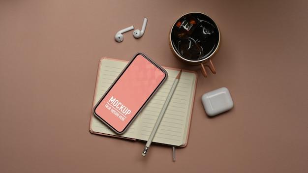 Vista superior da área de trabalho com maquete de smartphone, acessórios no notebook e xícara de café