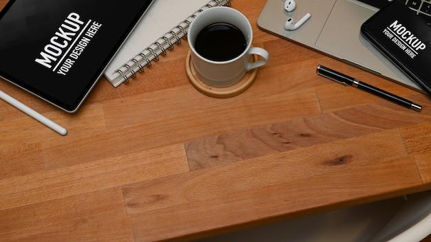 Vista superior da área de trabalho com maquete de smartphone e tablet e material de escritório