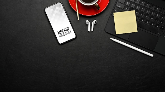 Vista superior da área de trabalho com maquete de smartphone, teclado e acessórios