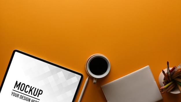 Vista superior da área de trabalho com maquete de tablet e xícara de café
