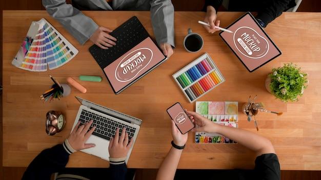 Vista superior da equipe de designer, informando sobre o projeto com maquete de dispositivos