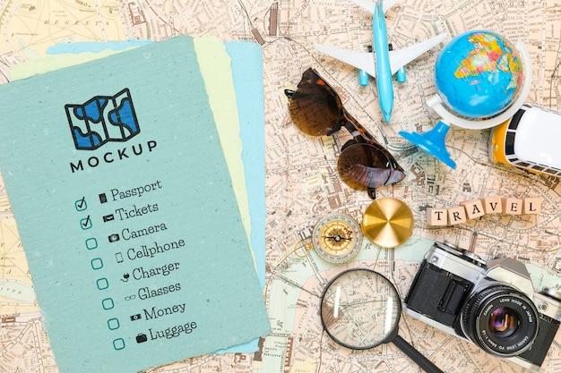Vista superior da lista de verificação com óculos de sol e globo para viajar