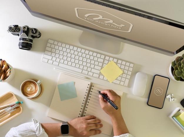 Vista superior da mão do empresário escrevendo na maquete de caderno em branco