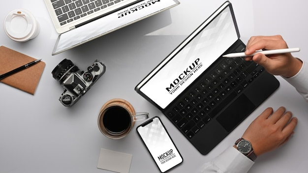 Vista superior da mão do empresário trabalhando com maquete de tablet e smartphone