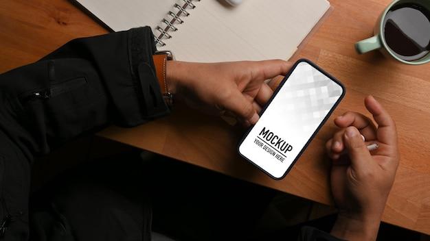 Vista superior da mão masculina segurando o caderno de programação e a xícara de café com maquete de telefone