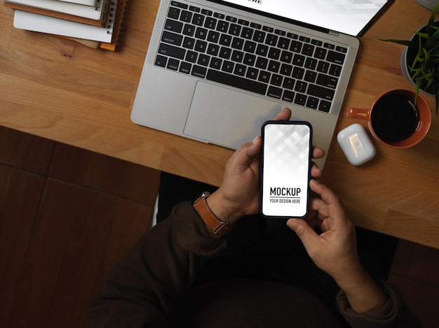Vista superior da mão masculina usando maquete de smartphone
