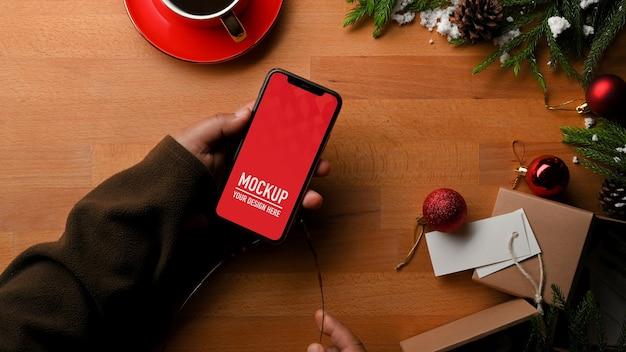 Vista superior da mão segurando a maquete do smartphone e as decorações de natal