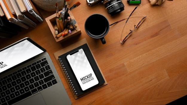 Vista superior da mesa de madeira com laptop, maquete de smartphone