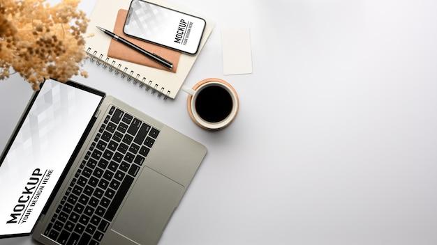 Vista superior da mesa de trabalho com maquete de laptop e smartphone