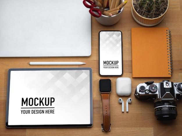 Vista superior da mesa de trabalho com tablet, smartphone, laptop, câmera e acessórios