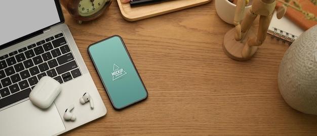 Vista superior da mesa do escritório em casa com maquete de smartphone