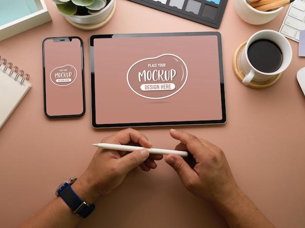 Vista superior das mãos do empresário segurando uma caneta stylus perto da maquete de dispositivos
